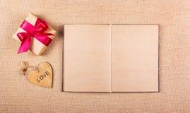 有弓的与心脏的礼物盒,卡片和与干净的床单的一本开放日志 复制空间 免版税库存图片