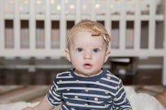 有弓的女婴在坐在她的有小儿床的卧室的头 库存照片