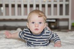 有弓的女婴在说谎在有小儿床的肚子的头 库存图片