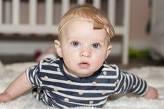 有弓的女婴在说谎在肚子的头在卧室 库存照片