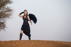 有弓的少妇和一个箭头在沙漠 免版税图库摄影