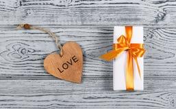 有弓的白色礼物盒和以心脏的形式木卡片在灰色木背景 木头和惊奇的心脏 免版税库存照片