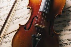 有弓的老古色古香的小提琴在纸笔记 免版税库存图片