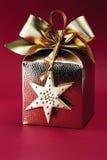 有弓的金黄被包裹的礼物盒反对红色背景 库存图片