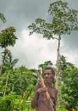 有弓箭的Korowai Kolufo老人在自然绿色森林背景 免版税库存照片