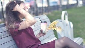 有引人注目的外观的一个美丽的愉快的女孩坐一条长凳在城市公园并且享用温暖 股票视频