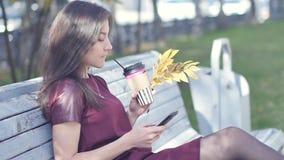 有引人注目的外观的一个美丽的愉快的女孩坐一条长凳在有一个电话的一个城市公园在她的手上 股票录像