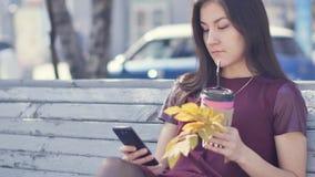 有引人注目的外观的一个美丽的愉快的女孩坐一条长凳在有一个电话的一个城市公园在她的手上 影视素材