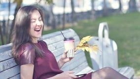 有引人注目的外观的一个美丽的愉快的女孩坐一条长凳在有一个电话的一个城市公园在她的手上 股票视频
