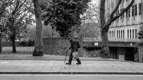 有弯的姿势的年长绅士走用棍子的 免版税库存图片