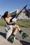 有弹吉他的冰鞋的妇女 免版税库存照片