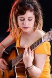 有弹吉他的dreadlocks的女性吉他弹奏者 免版税图库摄影