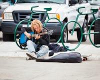 有弹在街道上的Dreadlocks的Yound人吉他 图库摄影