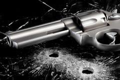 有弹孔的枪在玻璃 库存图片