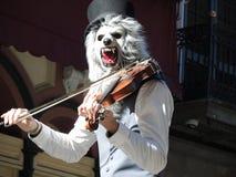 有弹小提琴的面具的音乐家 免版税库存照片