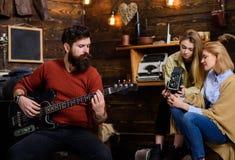 有弹电子吉他的被整理的胡子的人 在乡下晃动花费与家庭的音乐家时间 有胡子的人 免版税图库摄影