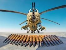 有弹药壳的军用战斗直升机在地面上 库存照片