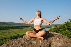 有强健的身体实践的瑜伽的深色的性感的运动妇女在反对蓝天的岩石 放松的片刻 库存图片
