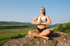 有强健的身体实践的瑜伽的深色的性感的运动妇女在岩石 背景蓝天 免版税库存图片