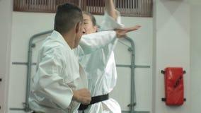 有强健的身体的一个年轻人和实践武术Goju-Ryu的妇女空手道 影视素材