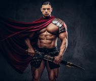 有强健的身体的残酷古希腊战士在摆在黑暗的背景的争斗设备 免版税图库摄影