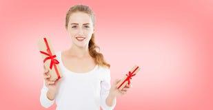 有当前箱子的美丽的青少年的妇女在桃红色背景隔绝的手上,假日圣诞节 免版税库存图片