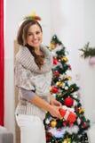 有当前配件箱的愉快的妇女在圣诞树附近 图库摄影