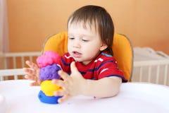 有彩色塑泥的可爱的婴孩在家 库存照片