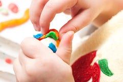 有彩色塑泥的婴孩的手 图库摄影