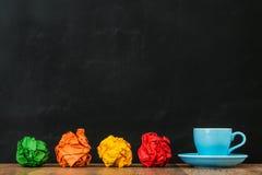 有彩虹一起纸球的蓝色咖啡杯 免版税库存图片