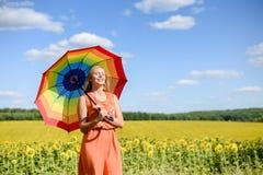 有彩虹伞的快乐的美丽的小姐 免版税库存照片