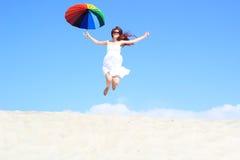 有彩虹伞跳跃的女孩 免版税库存图片