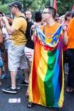 有彩虹对象和旗子的人们 图库摄影