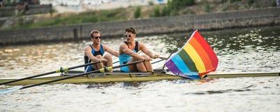 有彩虹旗子的划船者 库存照片