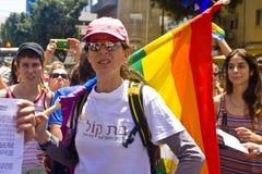 有彩虹标志的少妇在自豪感游行TA 免版税图库摄影
