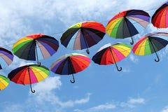 有彩虹的颜色的五颜六色的伞在蓝天的 免版税库存图片