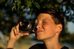 有影片照片照相机的年轻摄影师在庭院里 男孩在他的手上拿着一台照相机并且为树照相 库存照片