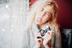 有影片照相机的年轻白肤金发的卷曲女孩模仿在咖啡馆的 免版税库存照片