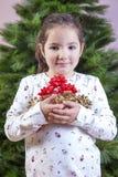 有很多丝带的微笑的小女孩圣诞树的12月 库存照片