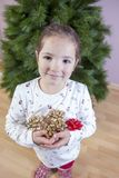 有很多丝带的微笑的小女孩圣诞树的12月 免版税库存照片