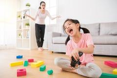 有很多杂乱玩具的逗人喜爱的小女孩孩子 免版税库存图片