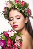有很多花的美丽的女孩在他们的头发和明亮的桃红色构成 春天图象 秀丽表面 库存照片