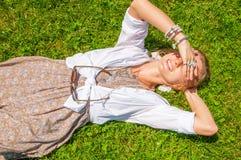 有很多辅助部件的美丽的boho样式妇女在绿草说谎 愉快的mometn 免版税库存图片