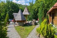 有很好面对石头的庭院的一个木的房子在森林中间汽车来了到访客 免版税库存照片