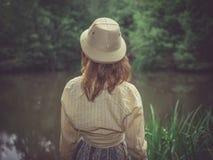 有徒步旅行队帽子的少妇由池塘在森林里 库存照片