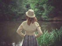 有徒步旅行队帽子的少妇由池塘在森林里 免版税图库摄影