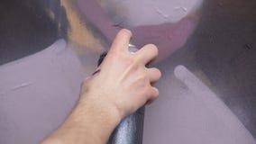 有得出在墙壁上的一张新的街道画的喷壶的一只手 得出在木的一张街道画的过程的照片 图库摄影