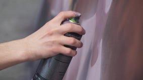 有得出在墙壁上的一张新的街道画的喷壶的一只手 得出在木的一张街道画的过程的照片 库存图片