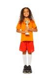 有得奖的杯子的小非洲女孩在体育比赛 免版税库存照片
