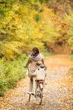 有循环在秋天公园的儿子的年轻母亲 库存图片